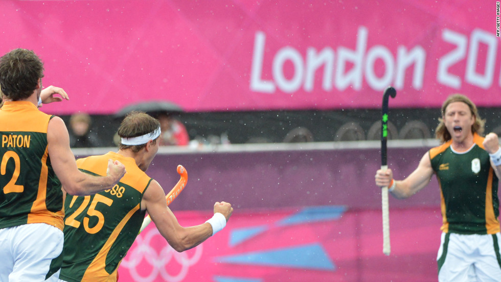 Members of the South African men's field hockey team celebrate a goal against Pakistan during a preliminary round match.