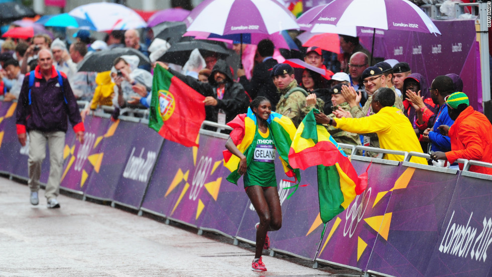 Wrapped in her nation's flag, Tiki Gelana of Ethiopia celebrates winning the women's marathon.