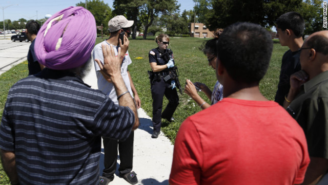 Bystanders look on as officer surrand the Sikh Temple of Wisconsin.