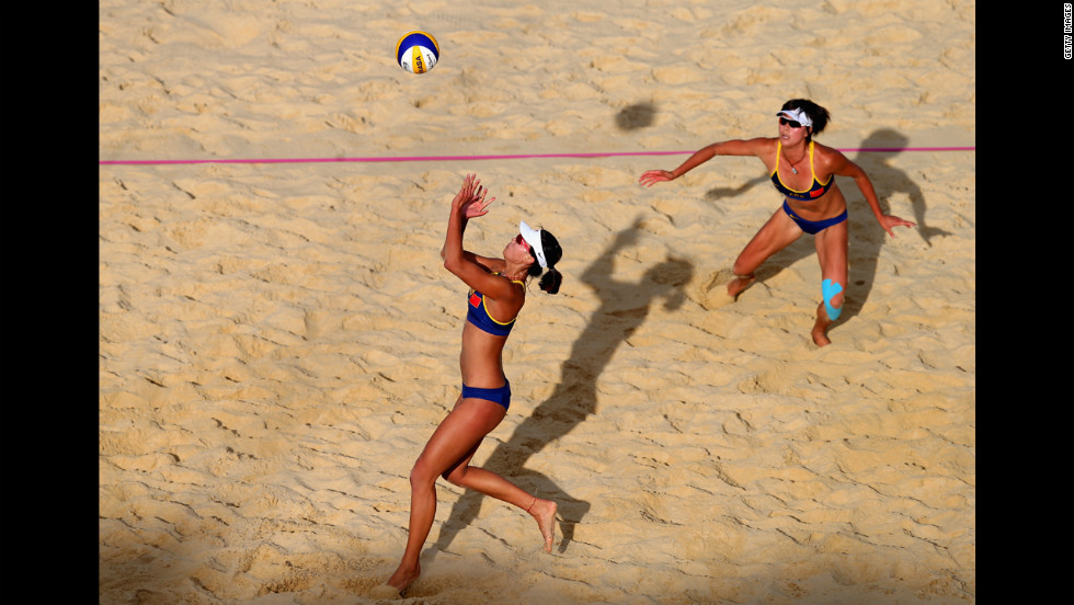 Xi Zhang of China, left, sets the ball for teammate Chen Xue during the women's beach volleyball quarterfinal match against Austria.