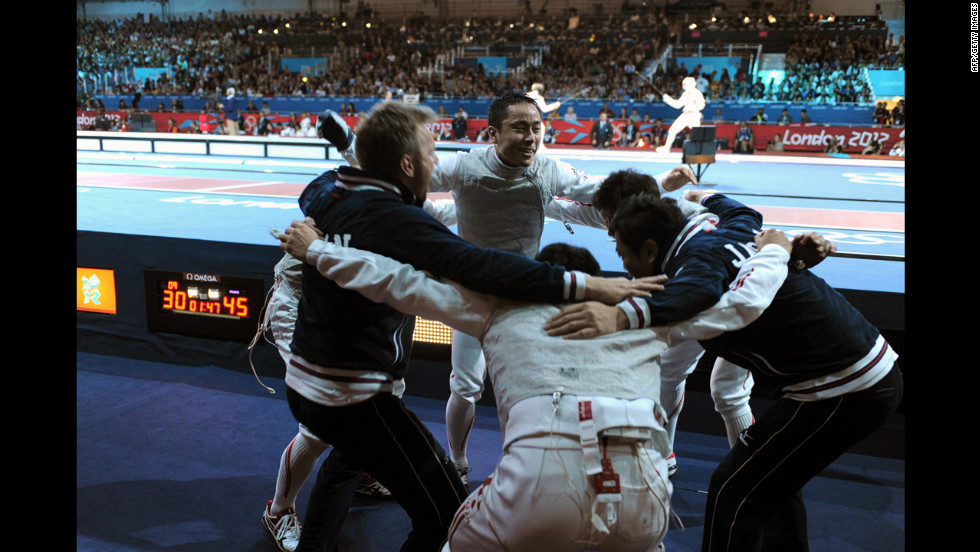 Team Japan celebrates defeating China during the men's foil team quarterfinals fencing event at the ExCeL center Sunday.