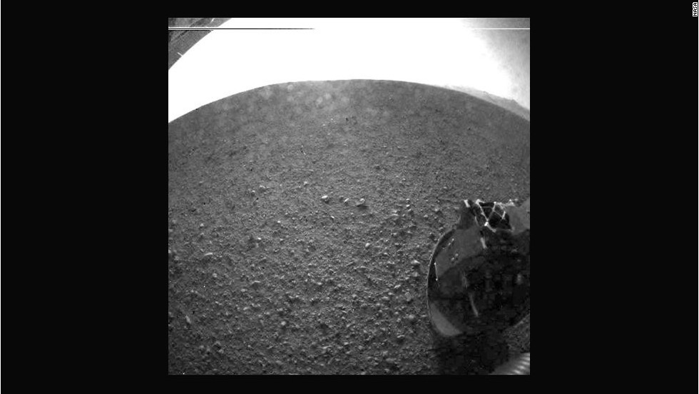 Another of the first images taken by the rover. The clear dust cover that protected the camera during landing has popped open. Part of the spring that released the dust cover can be seen at the bottom right, near the rover's wheel.