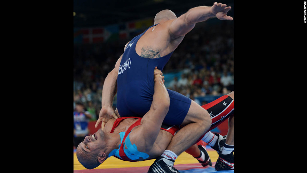 Egypt's Karam Mohamed Gaber Ebrahim, bottom, wrestles Poland's Damian Janiskowski during the men's Greco-Roman 84-kilogram semifinal.