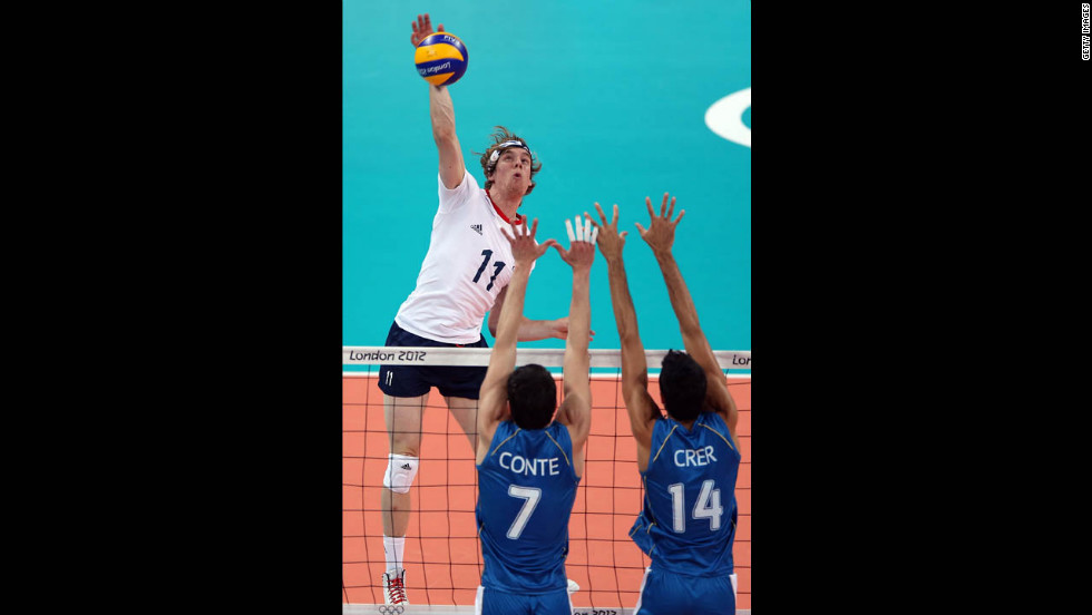 Joel Miller of Great Britain spikes the ball as Facundo Conte and Pablo Crer of Argentina defend during men's preliminary round Group A volleyball.