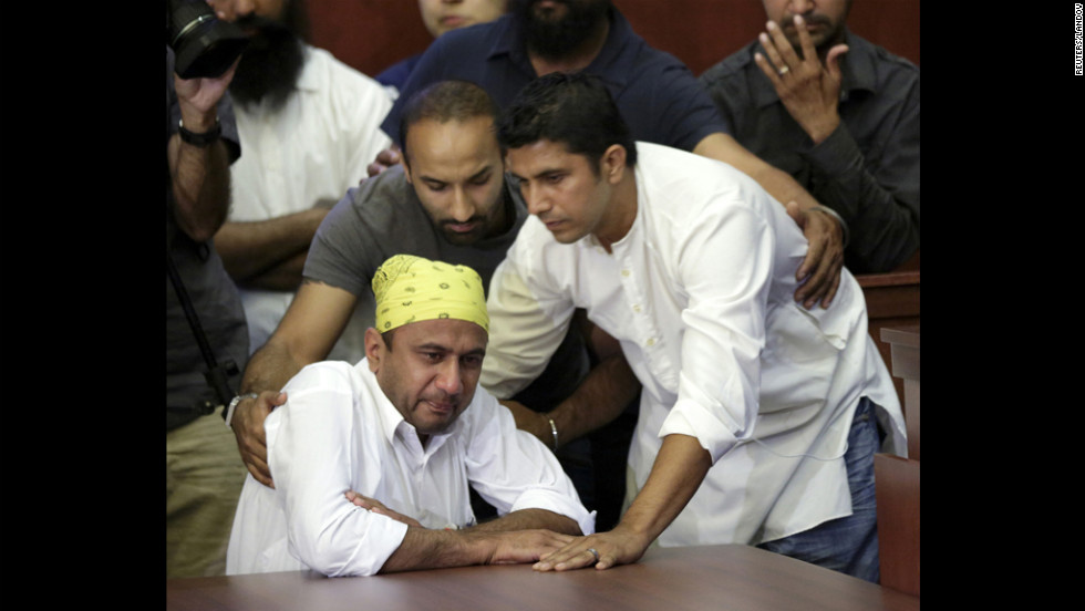 Harpreet Singh, left, and Amardeep Kaleka, right, whose father, temple President Satwant Kaleka, was killed in Sunday's shooting, cry during a news conference in Oak Creek.