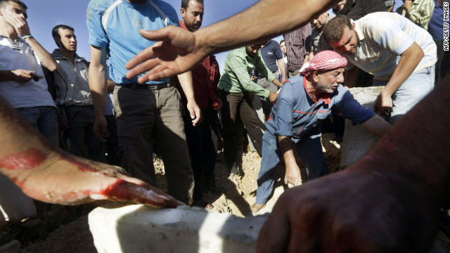 Syrian men bury their dead following heavy shelling by Syrian government forces in Qusayr, close to Homs, on July 3.