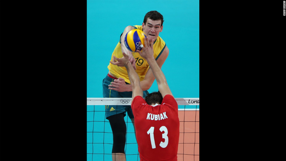 Thomas Edgar of Australia spikes the ball over Michal Kubiak of Poland during men's volleyball match at Earls Court.