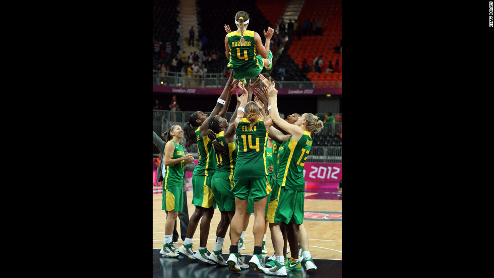 No. 4 Adriana Pinto is thrown into the air by teammates to honor her final game with the Brazil National Team after the women's basketball preliminary round match against Great Britain.