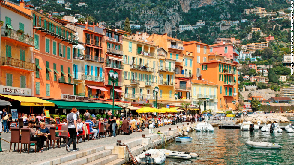 Colorful buildings provide a sun-splashed backdrop for restaurants along Villefranche-sur-Mer's lively quai. The Côte d'Azur's mild climate allows for outdoor dining and aperitif sipping most of the year.