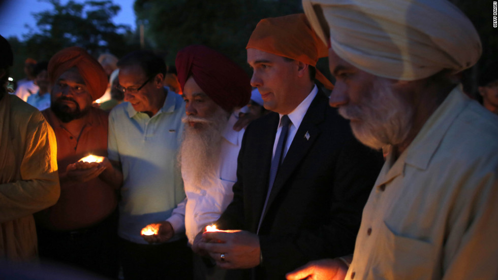 Wisconsin Gov. Scott Walker, along with members of the Sikh community, attends Monday's vigil at the Sikh Religious Society of Wisconsin for the victims of the shooting at the Sikh temple.