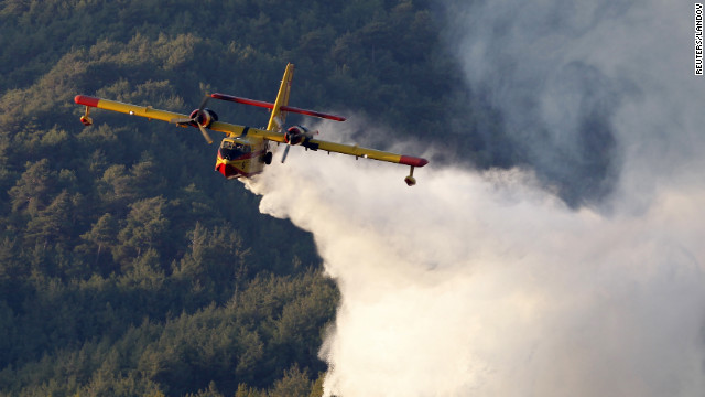 An aircraft dumps water to extinguish fires engulfing woodlands in the Mediterranean coastal town of Samandag in Hatay Province. Firefighters worked to bring under control a forest fire which engulfed 300 hectares in the Turkish province of Hatay.
