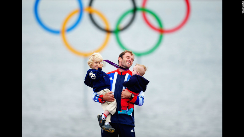 Silver medallist Nick Dempsey of Great Britain celebrates with his children Thomas-Flynn, left, and Oscar after the men's RS:X sailing.