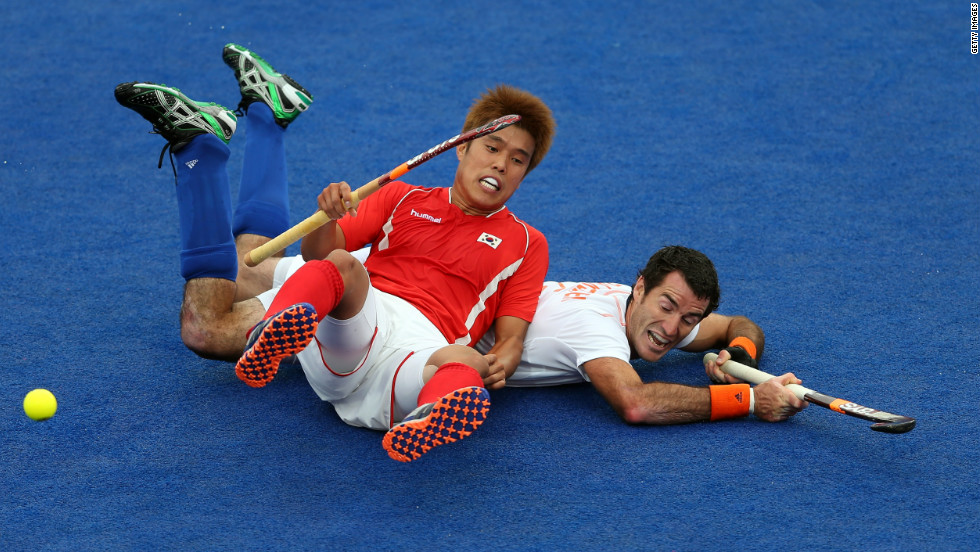 Hyo Sik You of South Korea falls on top of Marcel Balkestein of Netherlands during their men's field hockey match at Riverbank Arena Hockey Center.