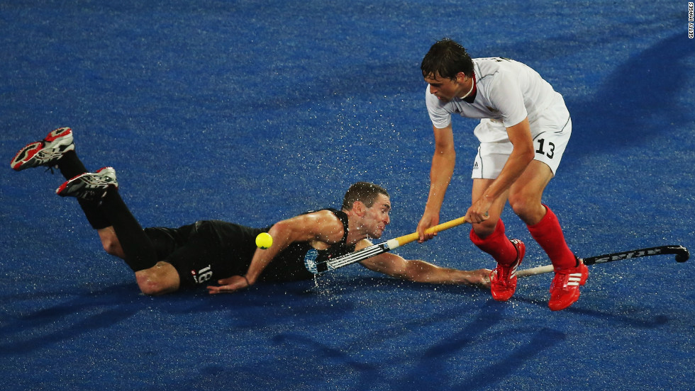 Tobias Hauke of Germany and Phillip Burrows of New Zealand challenge for the ball during the men's hockey match between Germany and New Zealand.