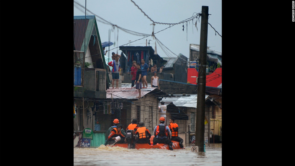 Rescuers in rubber boats evacuate residents from their homes in Tumana.