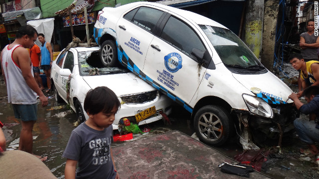 Residents look at vehicles washed up by floodwaters in Manila on August 8, 2012.