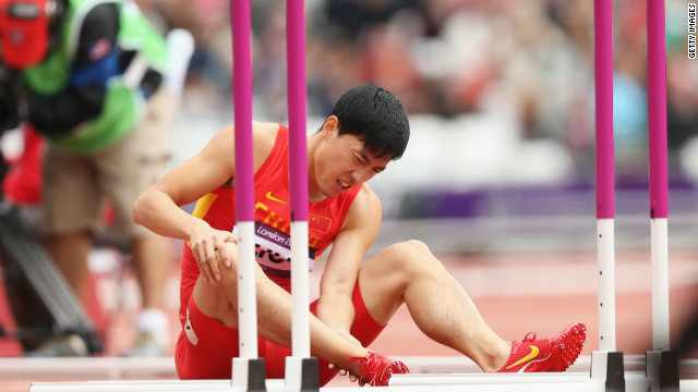 Chinese hurdler Liu Xiang sits on the track after falling seconds into the 110m heats at the 2012 Olympic Games, August 7.
