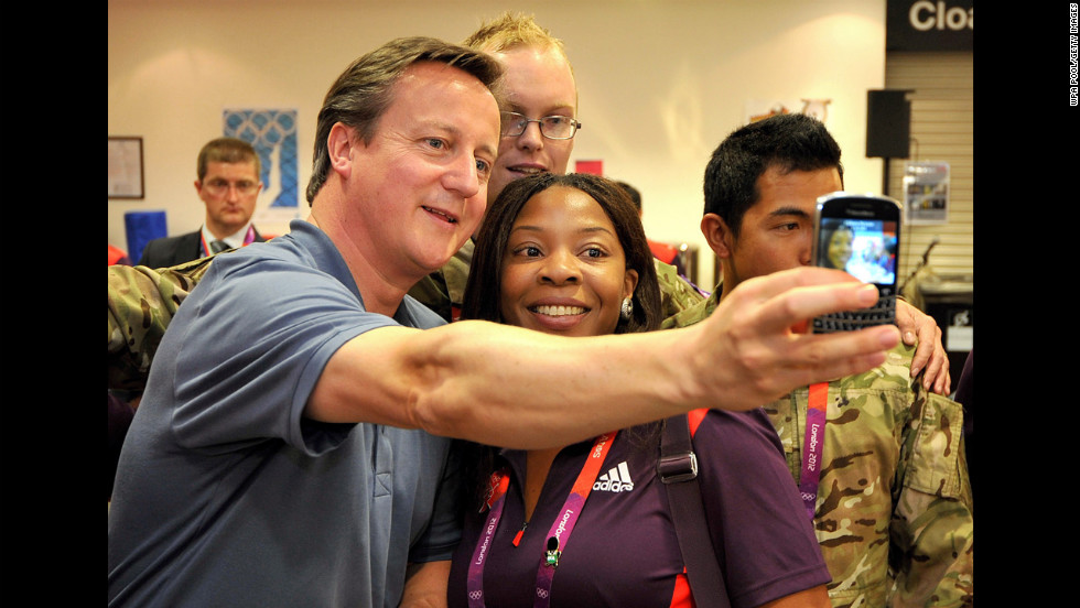 British Prime Minister David Cameron, left, takes a photo with Olympic volunteer Anita Akuwudike as he meets some of the volunteer work force at the ExCeL center in London.