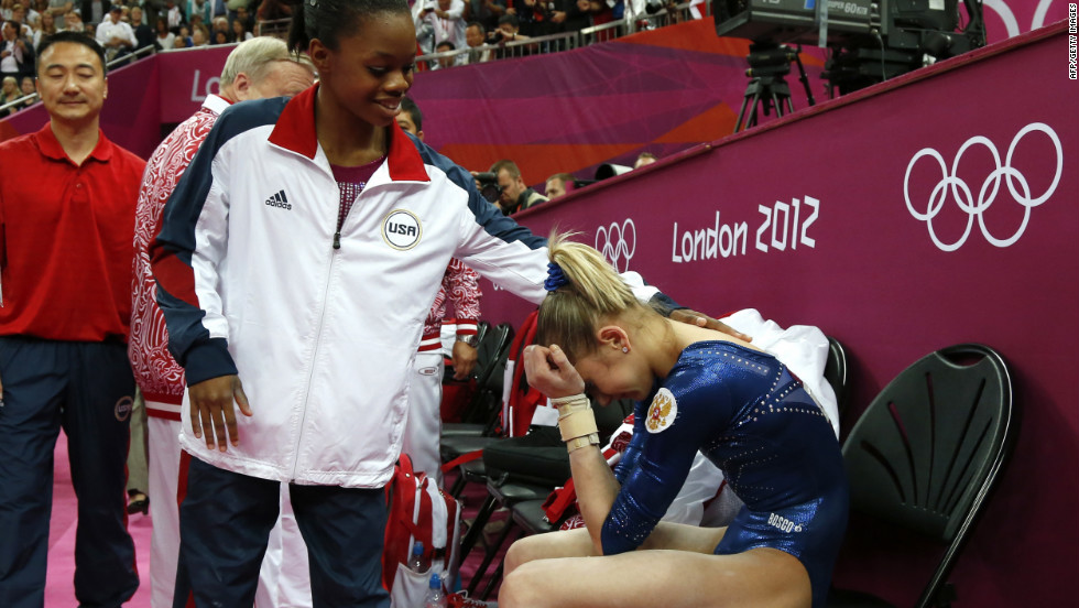 American gymnast Gabby Douglas, left, comforts Russia's Victoria Komova during the women's individual all-around competition. Douglas won the gold while Komova took silver.