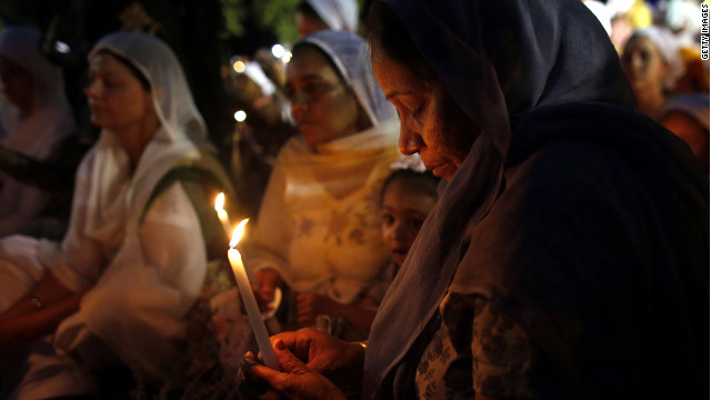 Mourners and supporters of the Sikh Temple of Wisconsin attend a candlelight vigil Tuesday at the Oak Creek Community Center.