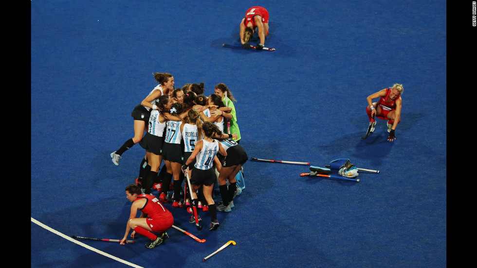 Anne Panter, Alex Danson and Crista Cullen of Great Britain slump to the ground as the Argentinian team celebrate their victory during the women's hockey semifinal match.