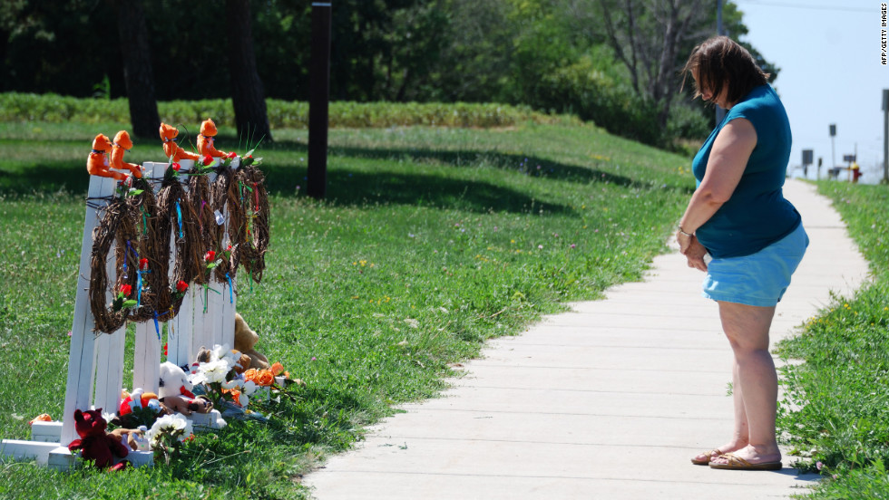 Peggy Renner-Howell bows her head after laying flowers Tuesday at a makeshift memorial near the Sikh Temple of Wisconsin in Oak Creek.