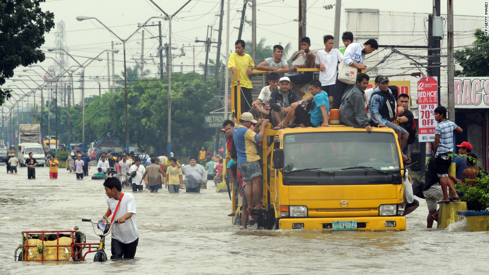 Residents commute through floodwaters in Cainta town in Rizal province, on Thursday.