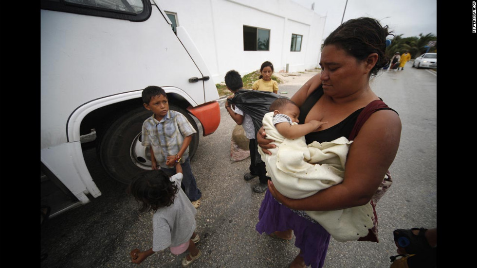 A woman and her children prepare to evacuate via bus as Ernesto approaches Mahahual on August 7.
