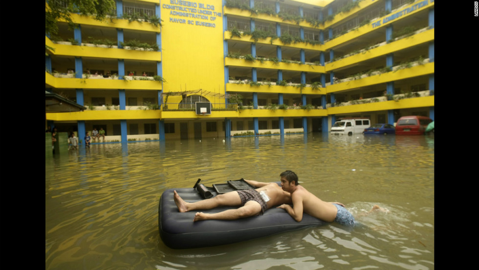 Flood victims rest on an inflated bed on Thursday at a flooded school turned into a temporary evacuation center.