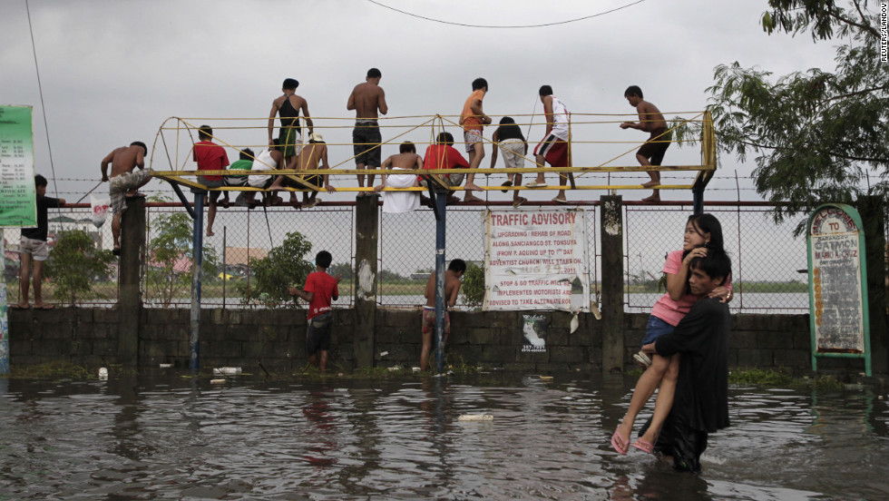 Residents wade through floodwaters caused by monsoon rains in Catmon, Malabon, north of metro Manila.