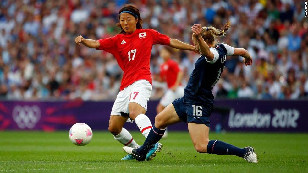 Yuki Ogimi of Japan moves the ball against Rachel Buehler of the United States.
