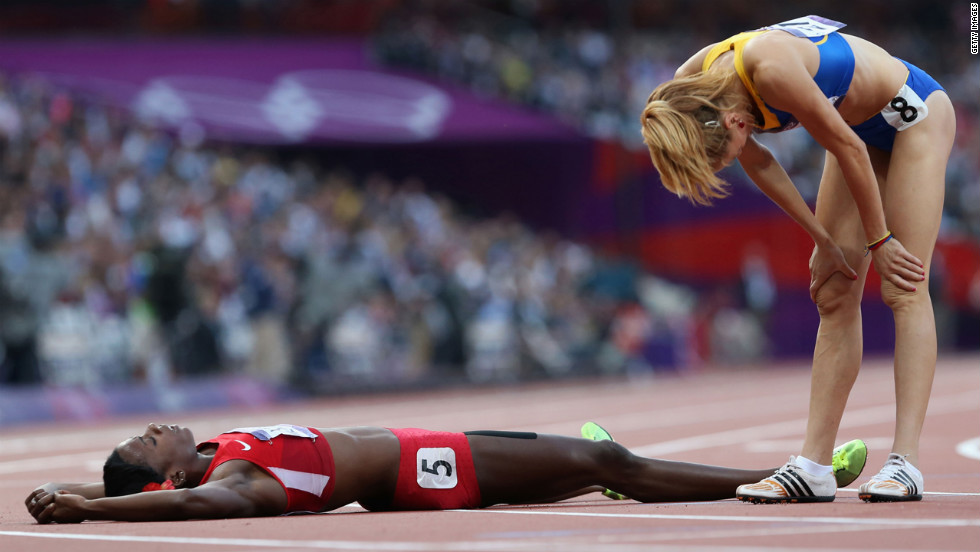 Alysia Johnson Montano of the United States lies on the ground next to Elena Mirela Lavric of Romania after the women's 800-meter semifinals.