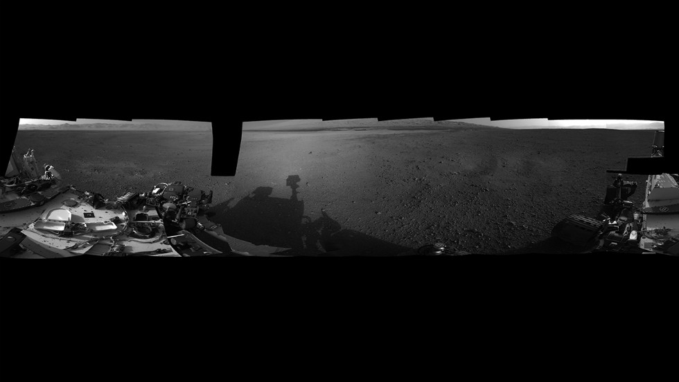 A panoramic photograph shows the Curiosity rover's surroundings at its landing site inside Gale Crater. The rim of Gale Crater can be seen to the left, and the base of Mount Sharp is to the center-right.