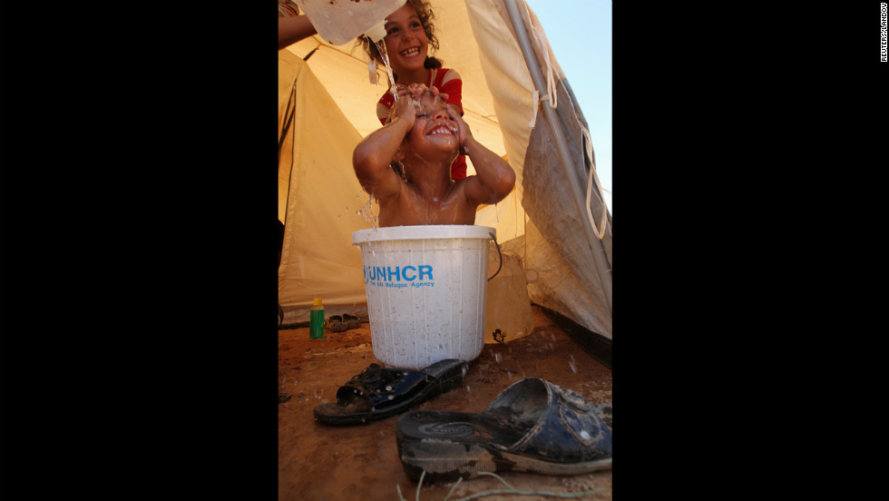 Syrian refugees bathe Wednesday at Al Zaatri U.N. camp in the Mafraq, Jordan, near the border with Syria.  The recent shelling has led thousands of residents to flee Syria.