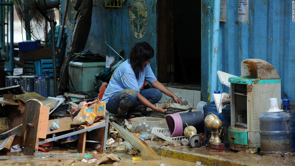 A resident cleans her mud-stained belongings Friday in suburban Manila. The weather has affected more than 2.4 million people, officials said.