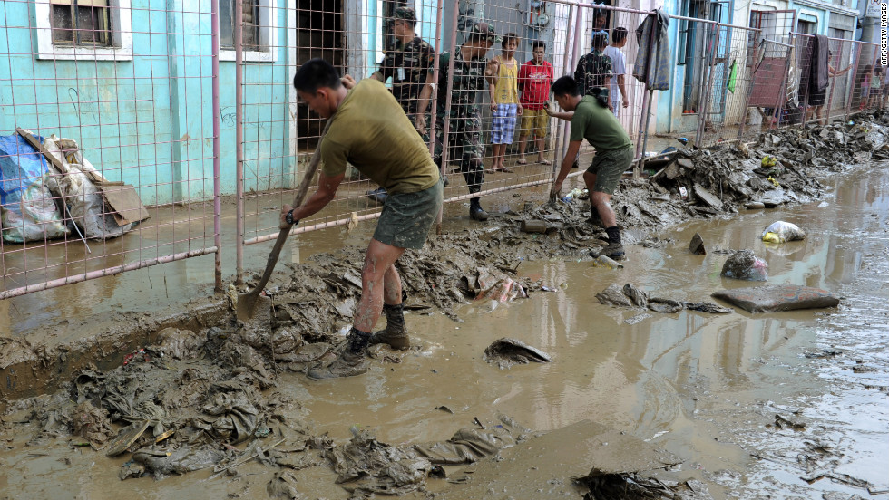 Philippine army corp engineers help residents clean streets Friday in a Manila suburb. It may take weeks for waters to recede in the lower-lying areas, forecasters say.