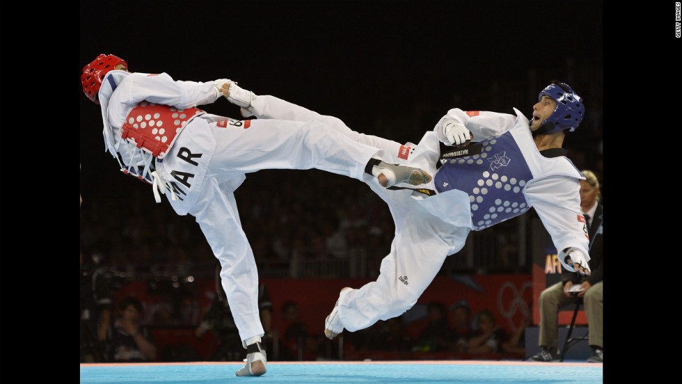 Morocco's Issam Chernoubi, left, battles Afghanistan's Nesar Ahmad Bahawi in the men's under 80-kilogram taekwondo bout.