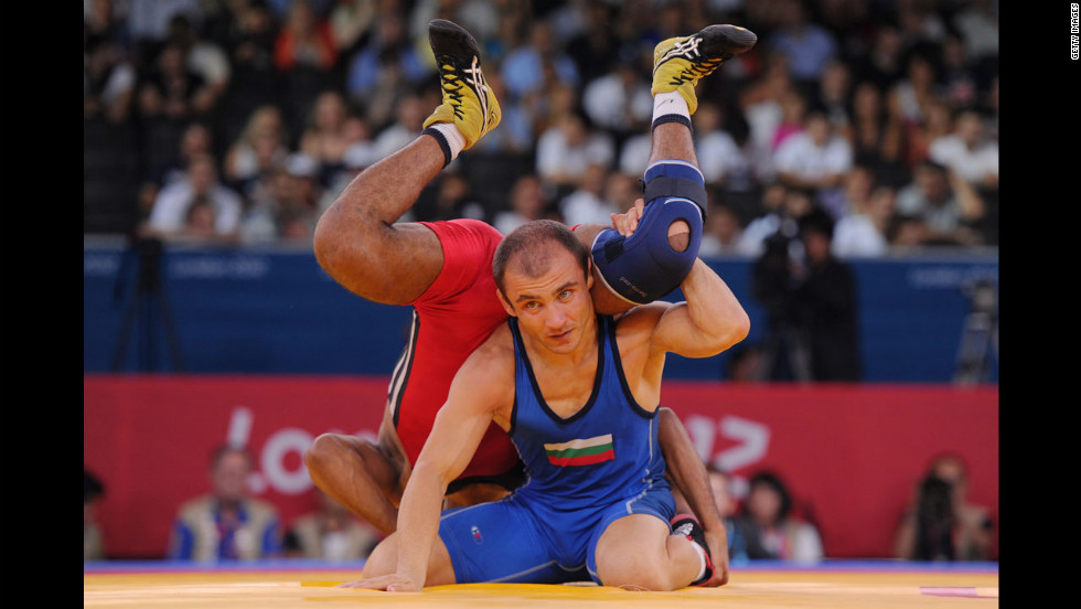 Egyptian wrestler Ibrahim Farag Abdelhakim Mohamed, in red, spars with Bulgarian Radoslav Marinov Velikov in the men's freestyle semifinal bout.