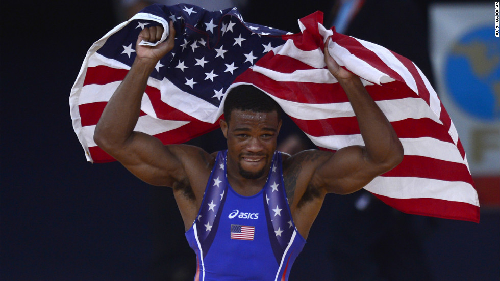 U.S. wrestler Jordan Ernest Burroughs celebrates with the national flag after defeating Iran's Sadegh Saeed Goudarzi in the men's freestyle gold medal match.