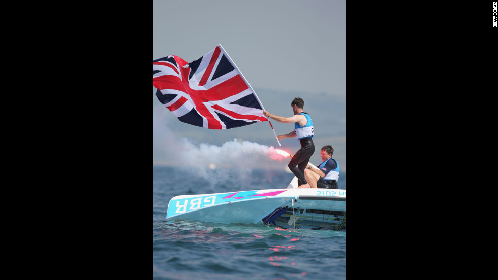 Luke Patience, left, and Stuart Bithell, right, of Great Britain let off flares as they celebrate finishing second and winning the silver medal in the men's 470 sailing.