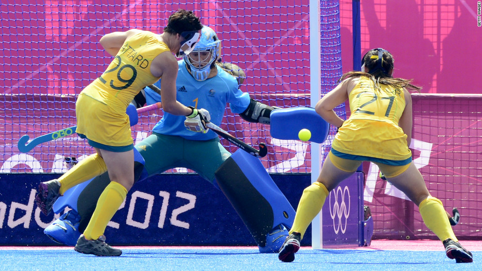 China's Zhang Yimeng, center, saves a shot from Australian Teneal Attard, left, as Attard's teammate Jayde Taylor stands by during the women's field hockey classification match.