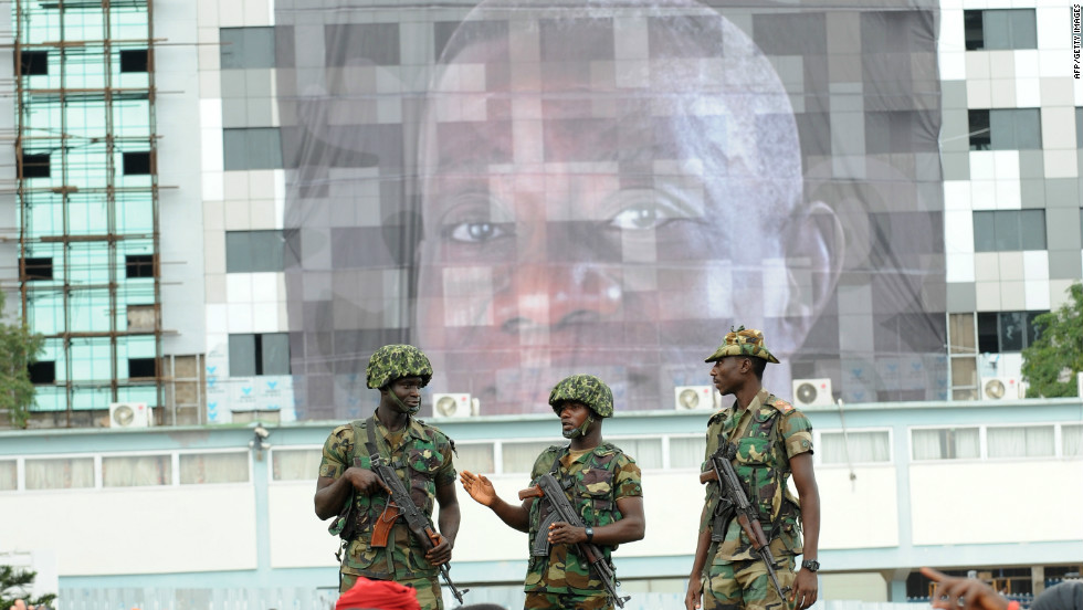 Soldiers stand on a platform behind mourners queuing Thursday outside the parliament to pay tribute to Mills.