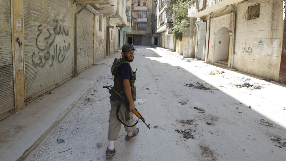 A Free Syrian Army fighter walks on an empty street in the Salaheddine neighborhood.