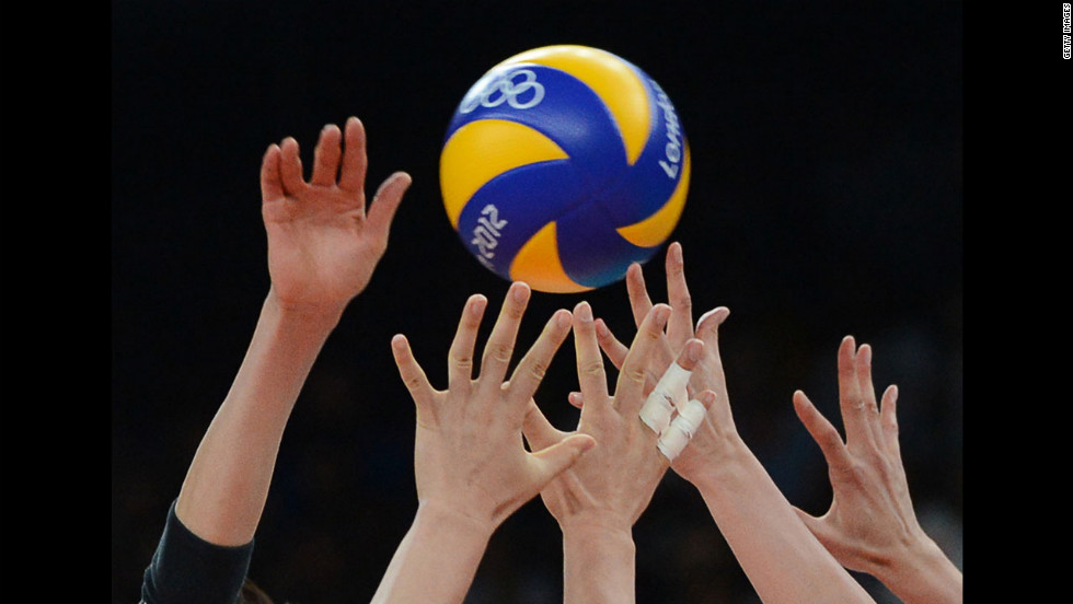 Japanese and South Korean players stretch for the ball during the women's volleyball bronze medal match.