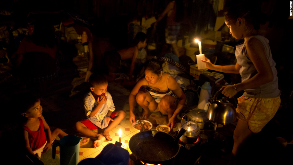 Flood victims use candles for light as they cook dinner at a crowded evacuation center on Saturday, August 11, in Manila, Philippines.