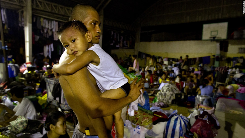 A flood victim holds his son at a crowded evacuation center in Manila.