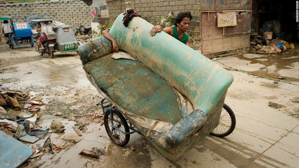 A man uses a bicycle to transport a sofa chair in Tomana slum following floods that submerged 80% of Manila.