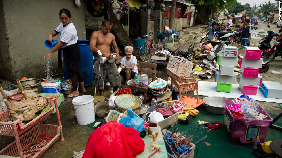 Flood victims clean their goods outside their house after water receded from their homes in the river bank slum.
