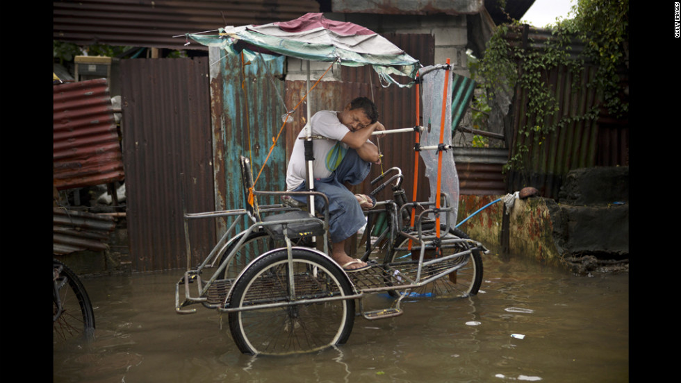 A pedicab driver sleeps on his vehicle along a flooded street in Manila.