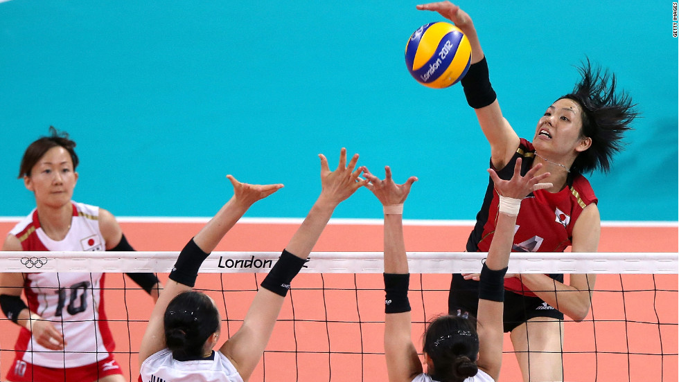 No. 14 Saori Sakoda of Japan spikes the ball against No. 13 Dae-Young Jung and No. 20 Sook-Ja Lee of South Korea during a women's volleyball match.